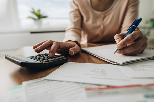 Close up of woman planning home budget and using calculator. 869247602