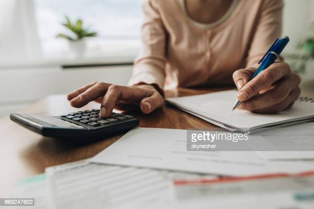 Close up of woman planning home budget and using calculator.