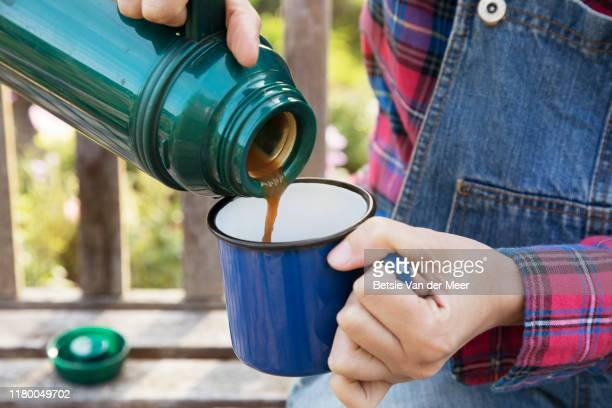 close up of woman pouring coffee from thermos flask in cup at allotment. - flask stock pictures, royalty-free photos & images