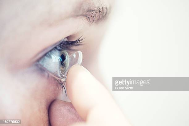 close up of woman putting in contact lens - contacts stock photos and pictures