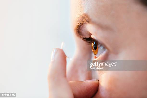 close up of woman putting in contact lens. - contacts stock photos and pictures