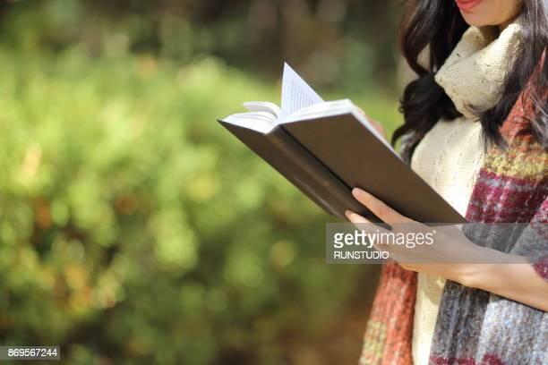 close up of woman reading  book in autumn park - literatura - fotografias e filmes do acervo