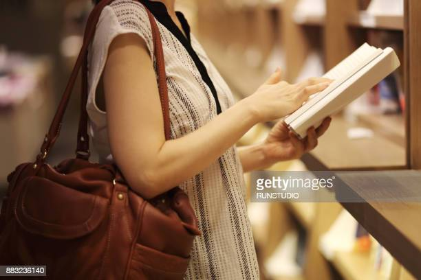 Close up of woman reading book in bookstore