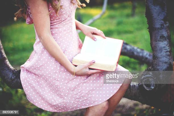 Close up of woman reading book in tree