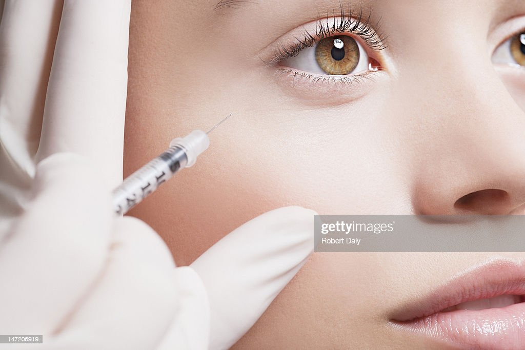 Close up of woman receiving botox injection under eye : Stock Photo