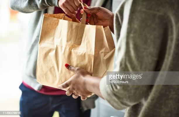 close up of woman receiving take away food delivery - dranken en maaltijden stockfoto's en -beelden