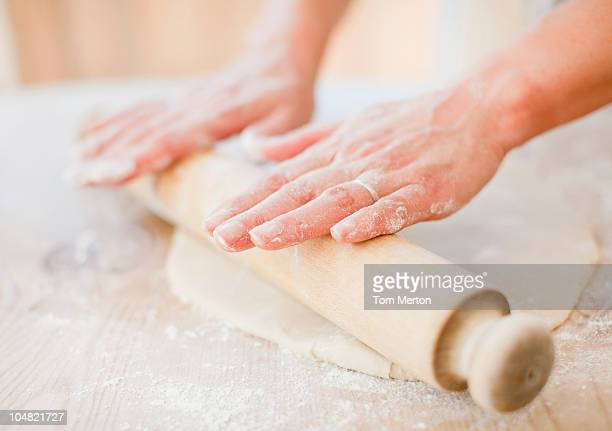 Close up of woman rolling dough with rolling pin on kitchen counter