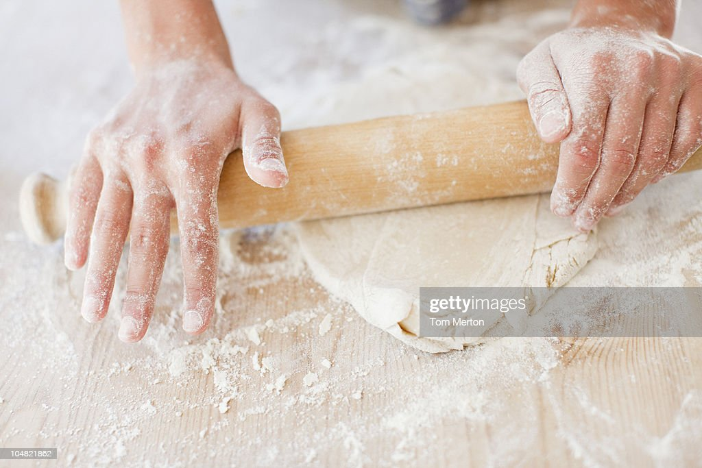 Close up of woman rolling dough with rolling pin : Stock Photo