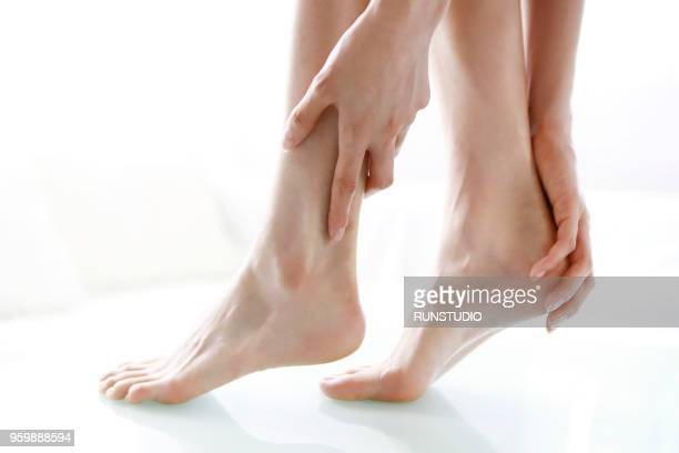 close up of woman rubbing feet - japanese women feet stock photos and pictures