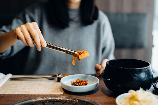 Close up of woman serving fresh kimchi on plate while having meal in a Korean restaurant - gettyimageskorea