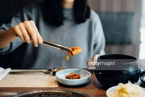 close up of woman serving fresh kimchi on plate while having meal in a korean restaurant - キムチ ストックフォトと画像