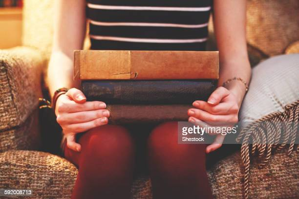 Close up of woman sitting on armchair holding books
