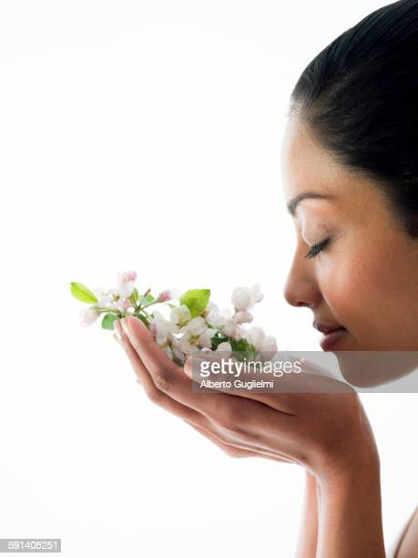 Close up of woman smelling flowers