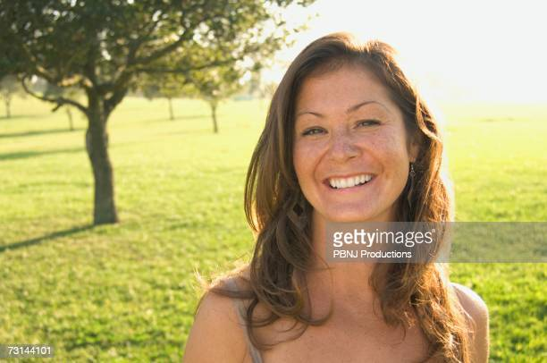 Close up of woman smiling in sunlit meadow