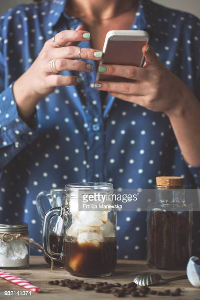 Close up of woman taking a photo of her coffee