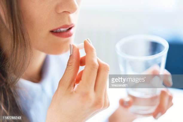 close up of woman taking pill - medicijnen innemen stockfoto's en -beelden