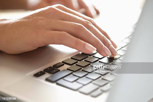 Close up of woman typing on laptop