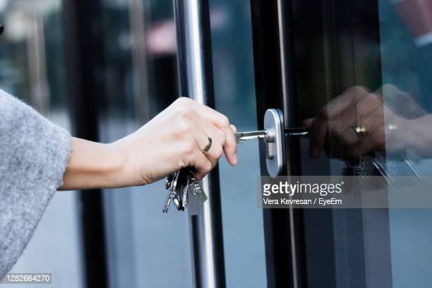 close up of woman unlocking entrance door with a key. person using key and locking apartment door. - unlocking stock pictures, royalty-free photos & images