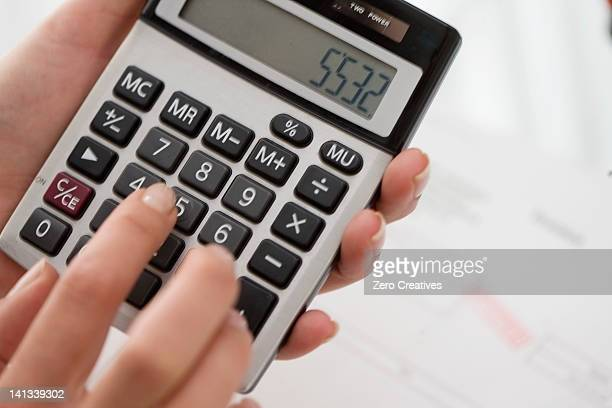 Close up of woman using calculator