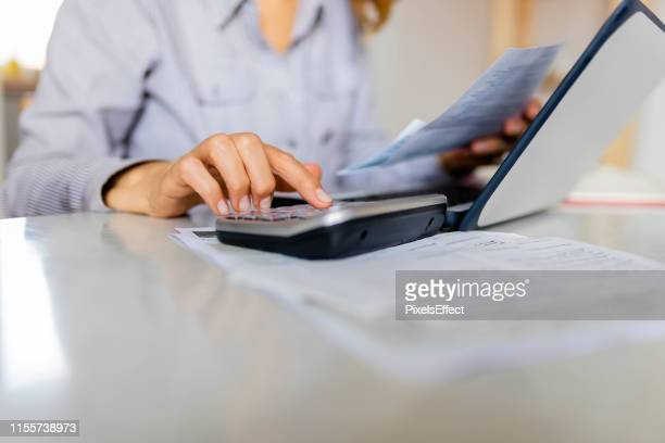 close up of woman using calculator while going through home finances. - calculator stock pictures, royalty-free photos & images