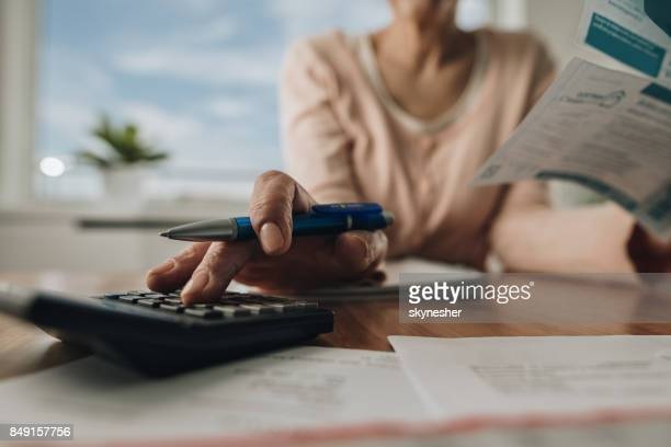Close up of woman using calculator while going through home finances.