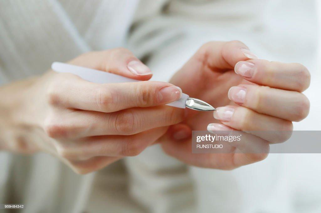 Close up of woman using cuticle pusher : Stock-Foto