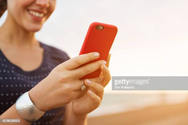 Close up of woman using smart phone on beach.