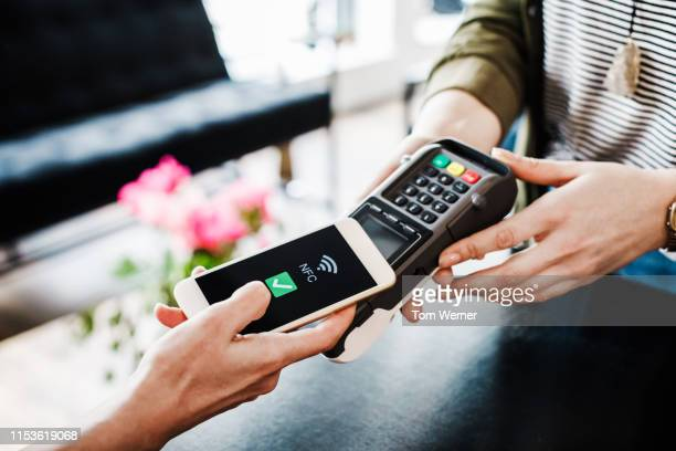 close up of woman using smartphone to pay for shopping - pagando - fotografias e filmes do acervo