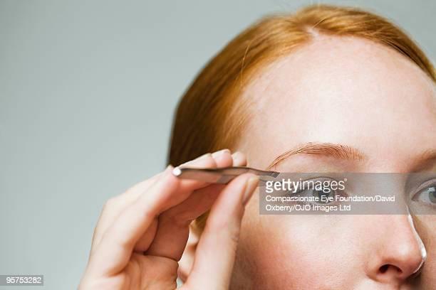 Close up of woman using tweezers on her eyebrow