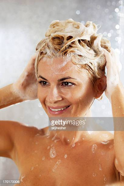Close up of woman washing her hair in a shower.