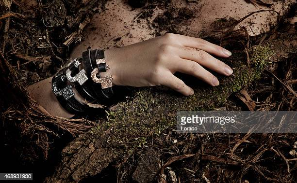 close up of woman wearing bracelets laying down in dirt