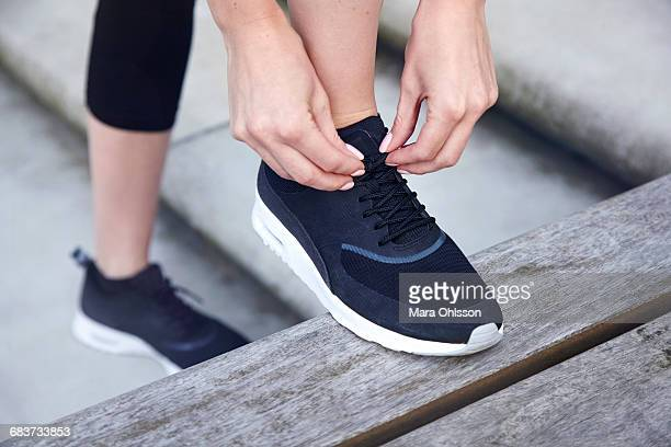 Close up of woman with foot raised on bench tying shoelace