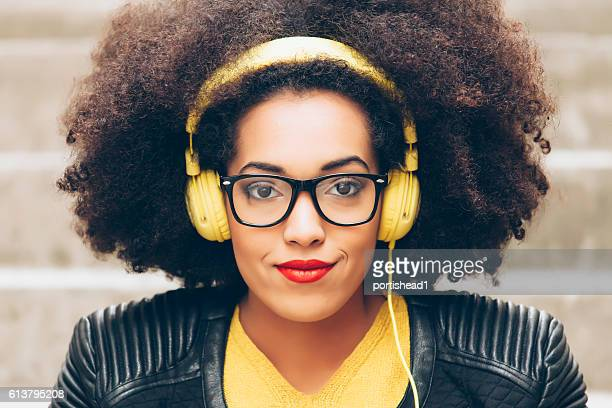 close up of woman with yellow headphones and curly hair - big hair stock photos and pictures