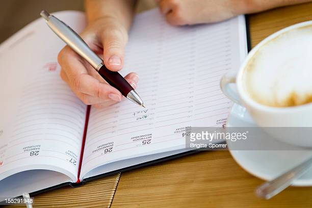 close up of woman writing in planner - kalender stock-fotos und bilder