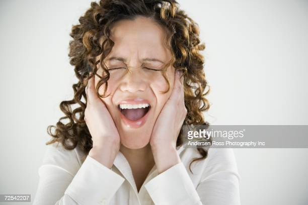 Close up of woman yelling and covering ears