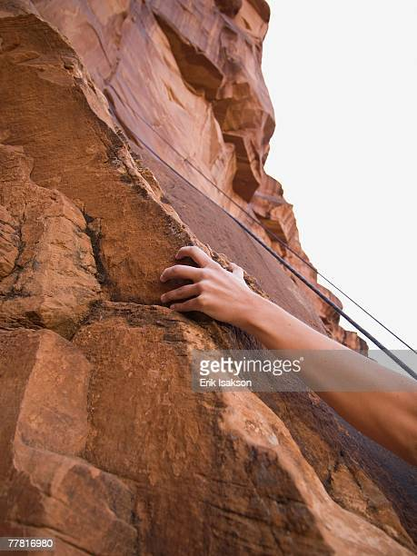 Close up of woman's arm rock climbing