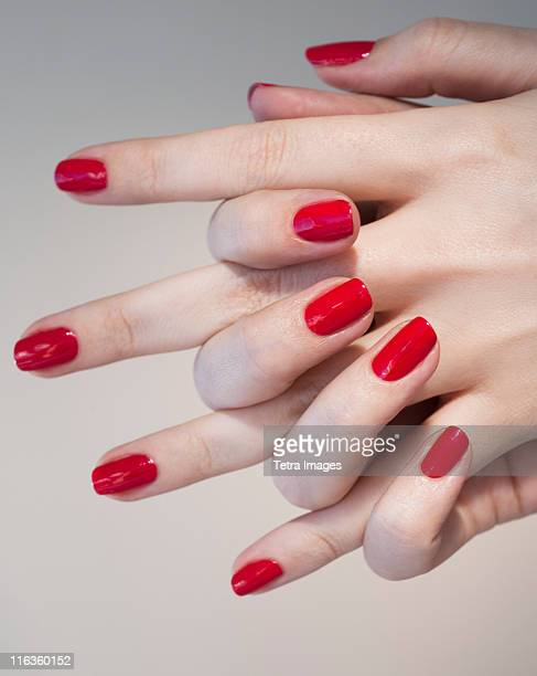Close up of woman's clasped hands with red nail polish