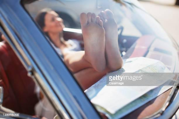 Close up of womanÍs dirty feet on dashboard