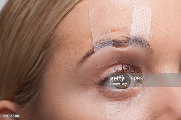 close up of woman's eye taped open - lid stock photos and pictures