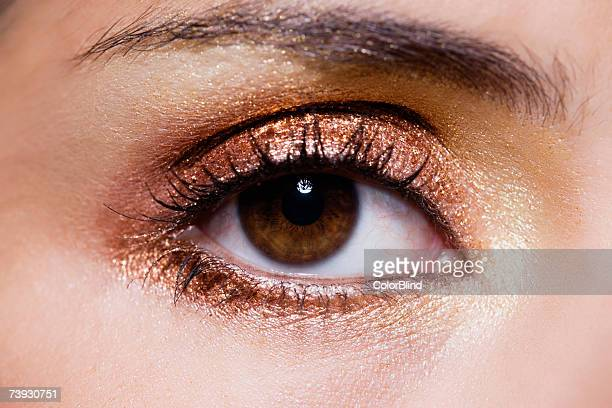 close up of woman's eye with gold eye make-up - bruin stockfoto's en -beelden