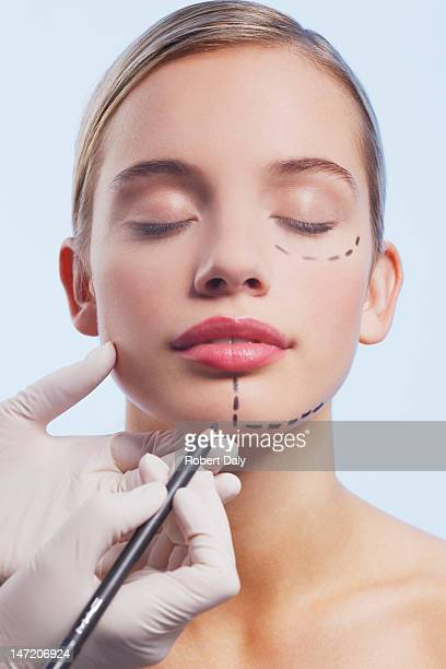 Close up of woman's face being marked with dotted lines