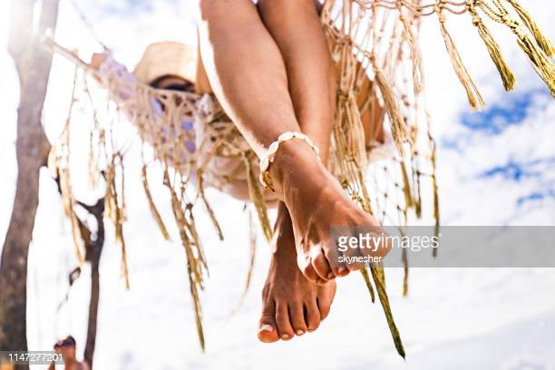 close up of woman's feet during her relaxing summer day in hammock. - toe stock pictures, royalty-free photos & images