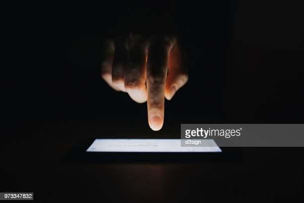 close up of woman's hand checking emails on smartphone  against black background - elektronische organiser stockfoto's en -beelden