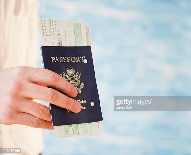 Close up of woman's hand holding passport, studio shot