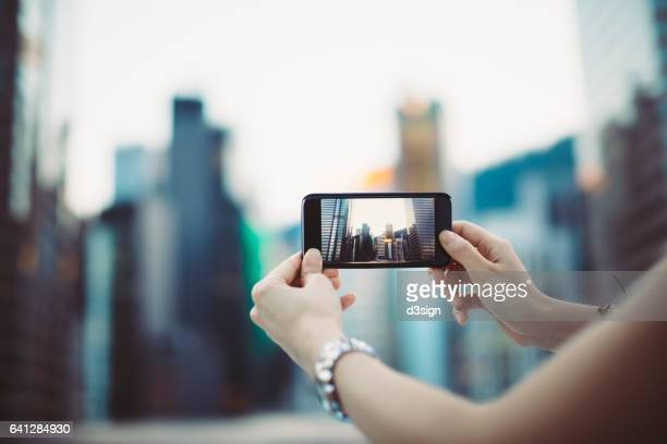 Close up of woman's hand photographing pictures of city skyline with smartphone