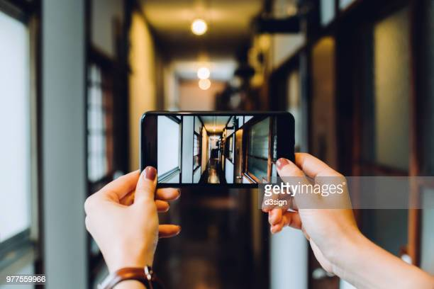 close up of woman's hand photographing with smartphone the architecture of traditional japanese house - photo messaging stock pictures, royalty-free photos & images