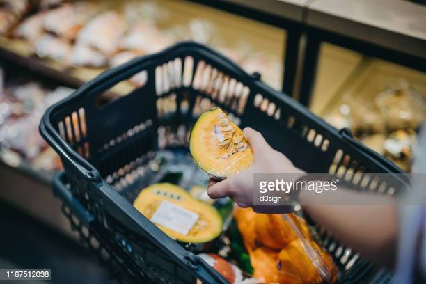 close up of woman's hand putting fresh produce into shopping cart while grocery shopping in supermarket - basket stock pictures, royalty-free photos & images