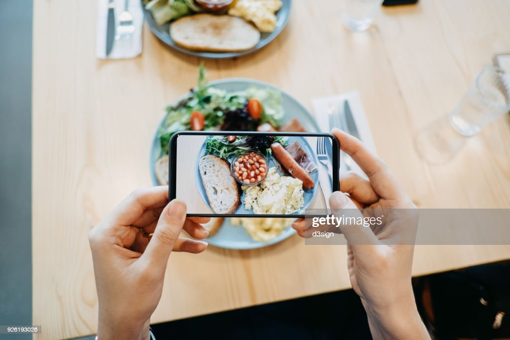 Close up of woman's hand taking a photo of fresh breakfast with smartphone : Stock Photo
