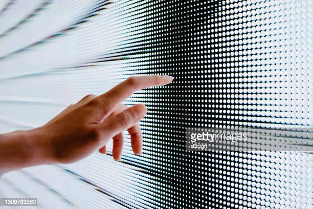 close up of woman's hand touching illuminated led display screen, connecting to the future - liquid crystal display stock pictures, royalty-free photos & images