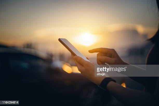 close up of woman's hand typing on the smartphone in the city in front of cars at beautiful sunset - 5g foto e immagini stock